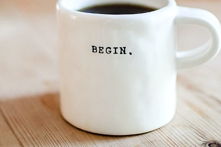 """Image of a coffee mug with the word """"begin"""" printed on it"""