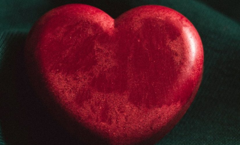Photograph of a red stone heart on a green background